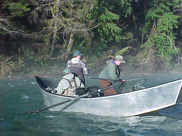 Guide Gordy with fish in net prepares to pull it in.
